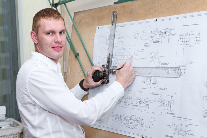 做工程项目的设计师由铅笔在绘图板 库存照片