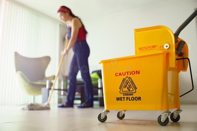 做差事的妇女在家清洗在桶的地板焦点 免版税库存图片