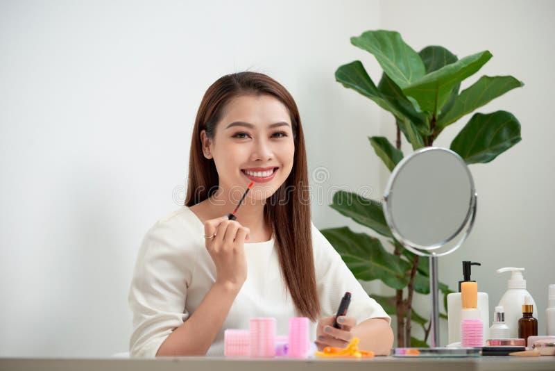 做年轻的美女在镜子附近化妆,坐在书桌 库存图片