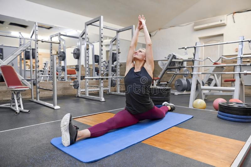 做年轻运动肌肉的妇女舒展在健身房的锻炼,女子实践的瑜伽 免版税库存图片