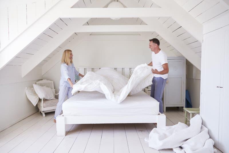 做床的夫妇佩带的睡衣在早晨 免版税库存图片