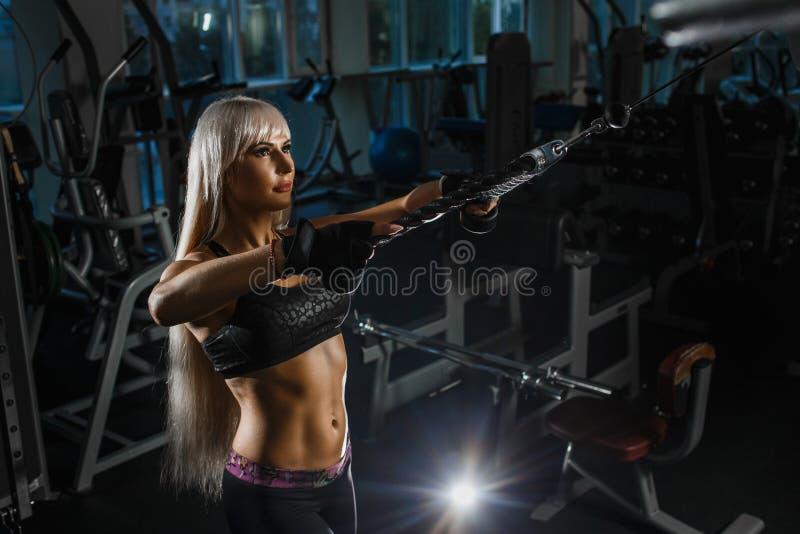 做引体向上的肌肉白肤金发的妇女训练有trx健身皮带的胳膊在健身房概念锻炼健康生活方式 免版税图库摄影