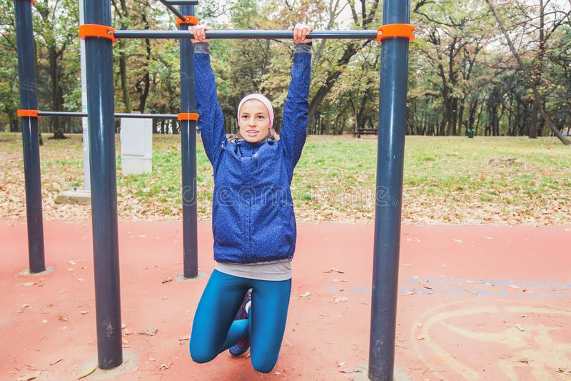 做引体向上的运动的女孩行使在室外健身房 库存照片