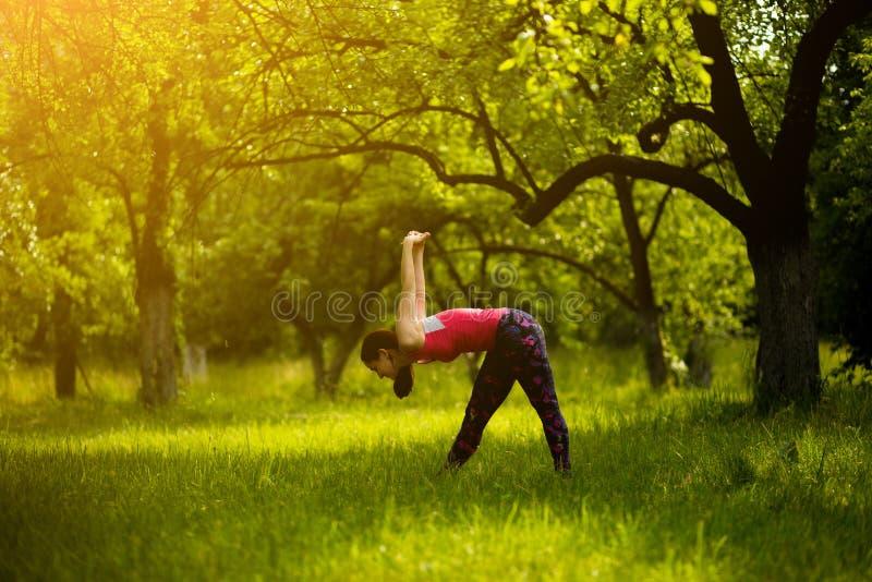 做强烈的旁边舒展姿势实践的瑜伽的妇女 库存图片