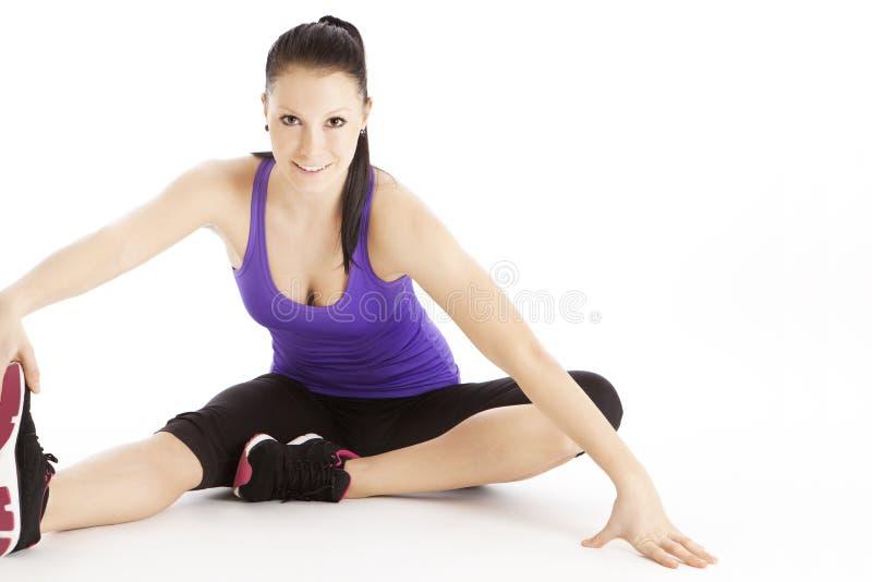 streching她的腿的妇女 图库摄影