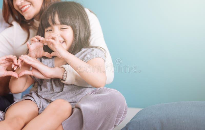 做心形的女孩坐在妈妈膝部 免版税库存照片