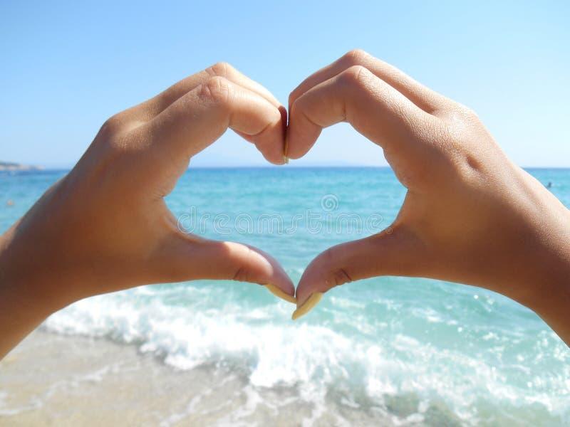 做心脏和blured明亮的蓝色海的手在背景中做波浪 免版税库存照片