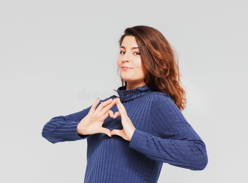 做心脏姿态用手的美丽的浪漫深色的女孩 免版税图库摄影
