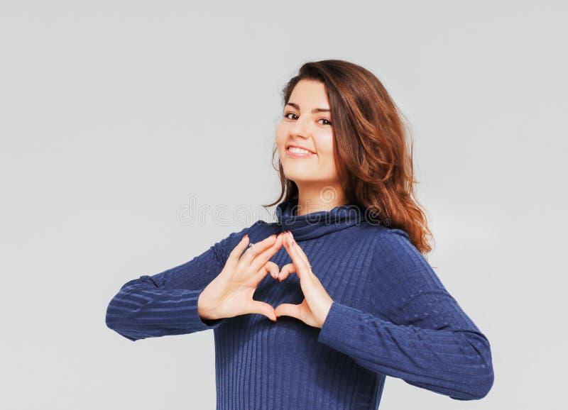 做心脏姿态用手的美丽的浪漫深色的女孩 免版税库存照片