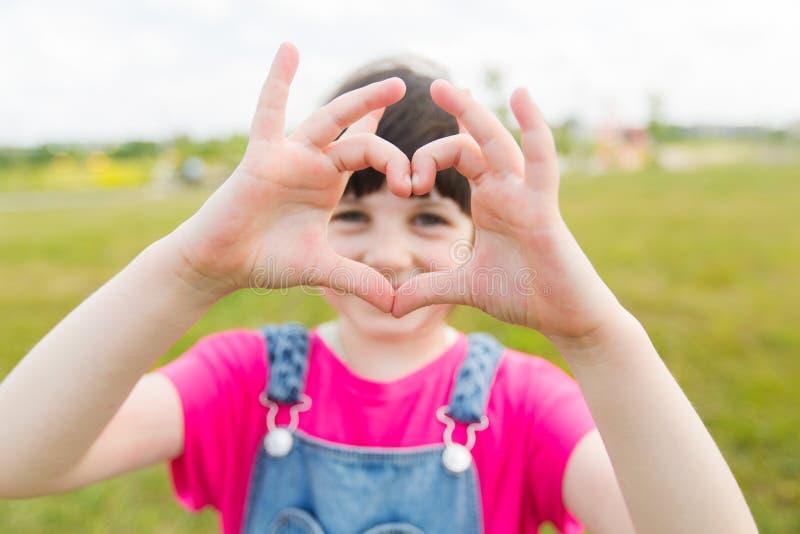 做心脏形状姿态的愉快的小女孩 免版税库存图片
