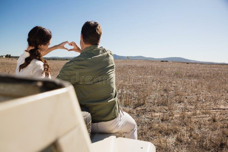 做心脏形状用手的夫妇背面图在公路车辆 免版税库存图片