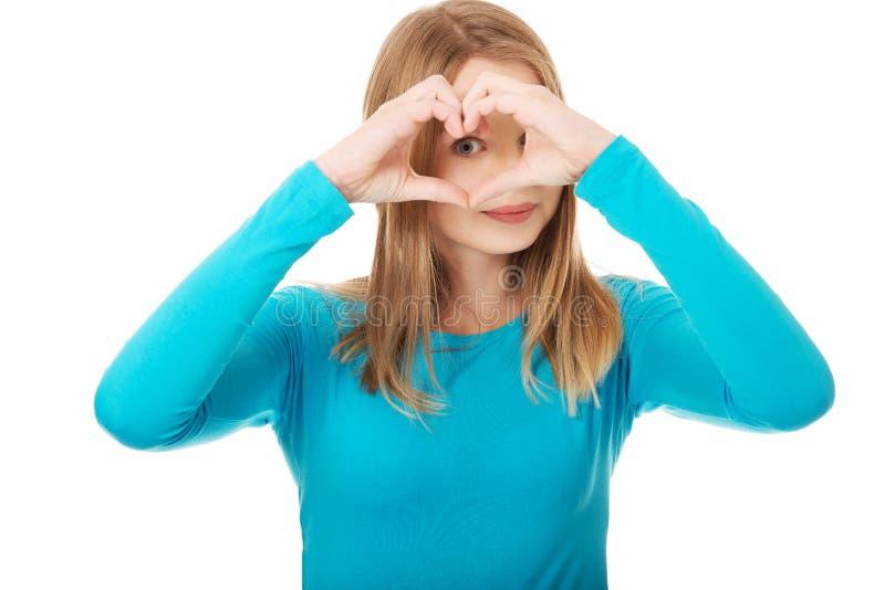 做心脏形状的微笑的少年妇女 免版税库存照片