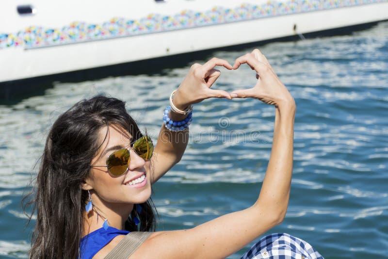 做心脏标志用手的年轻微笑的妇女在巴塞罗那 库存图片