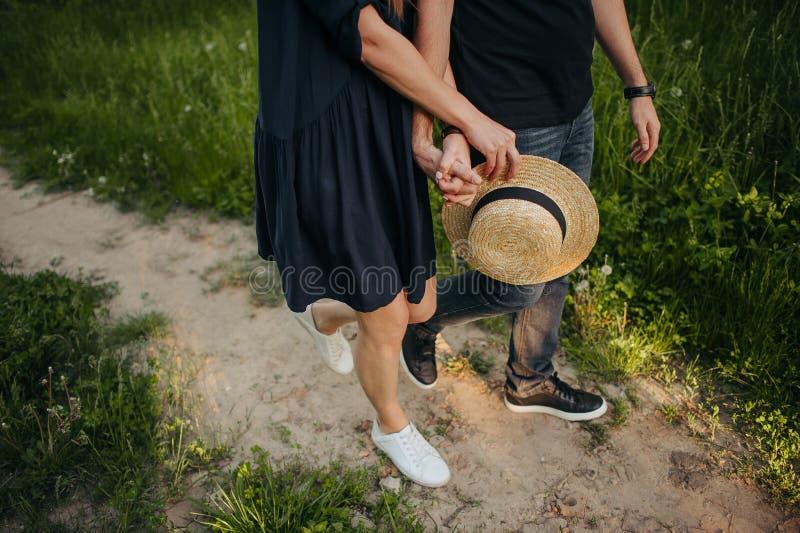做心脏标志的愉快的夫妇由有落日的手在背景中在美好的浪漫日落 免版税库存照片