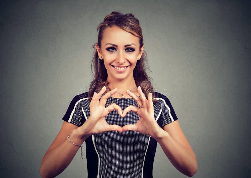 做心脏用她的手的愉快的妇女 库存照片