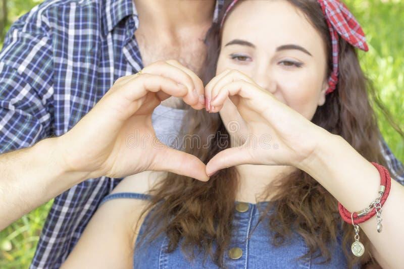 做心脏用手的年轻夫妇 遇见爱夏天野餐 免版税库存照片