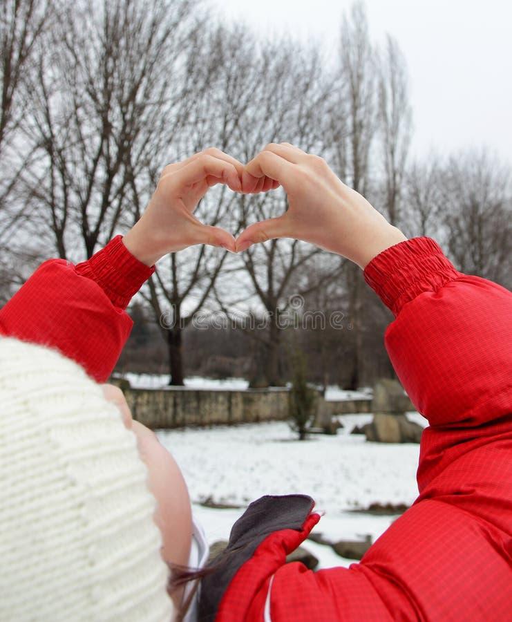 做心脏的女孩由手指 库存照片