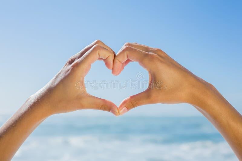 做心脏的女性手由海塑造 免版税库存图片