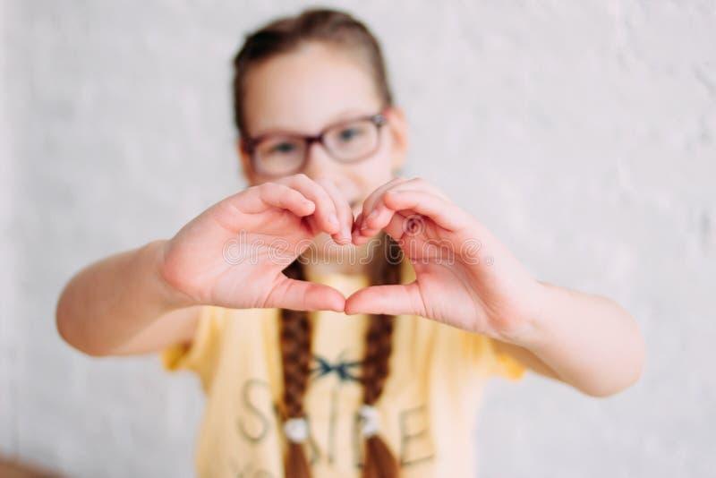 做心脏的黄色T恤杉的愉快的非离子活性剂女孩用人工在白色墙壁背景,选择聚焦 免版税库存图片