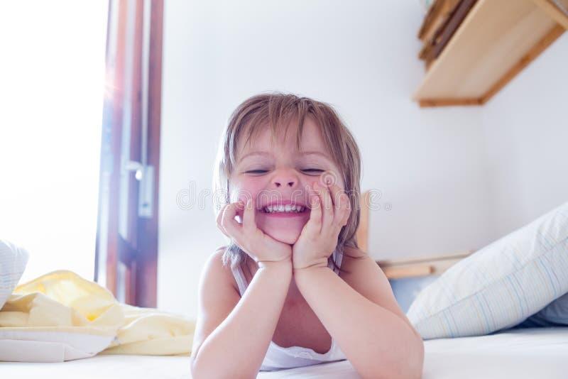做愉快的女孩的女儿微笑和在早晨面对看在父母` s床上的照相机 愉快的轻松的家庭生活 库存图片