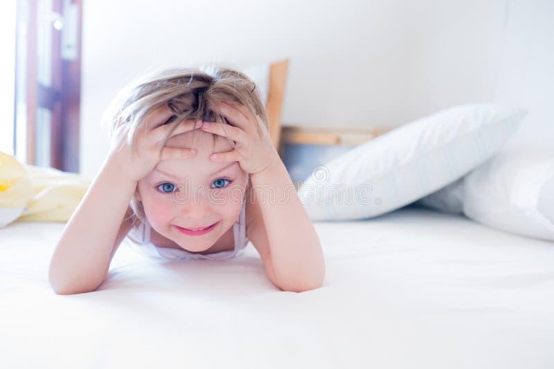 做愉快的女孩的女儿微笑和在早晨面对看在父母` s床上的照相机 愉快的轻松的家庭生活 免版税库存图片