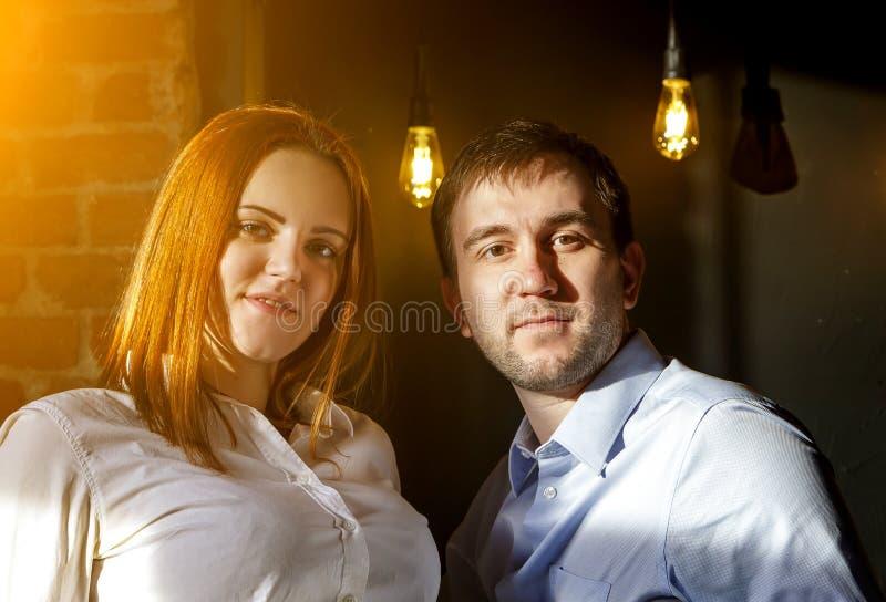 做愉快的面孔,明亮的阳光的滑稽的嬉戏的年轻夫妇在正确和热的电灯泡向高处发射内部在背景中 库存照片