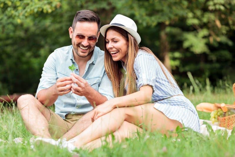 做愿望的美好的年轻夫妇在发现四片叶子三叶草以后 免版税库存照片