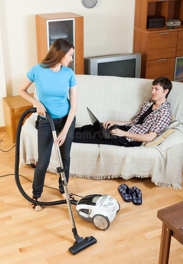 做房子清洁的妇女在人休息期间 库存照片