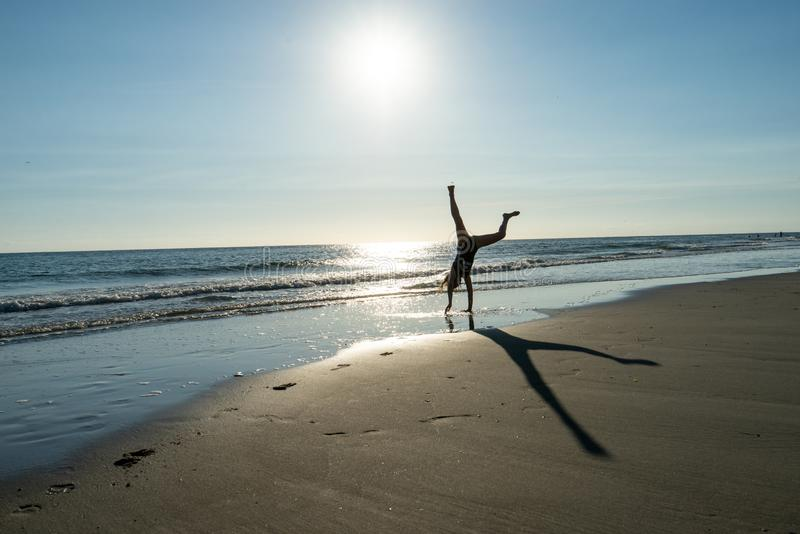 做手倒立的适合男性在晴朗的沙滩 免版税库存照片