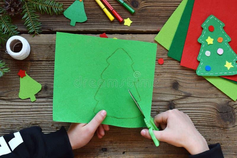做手工制造圣诞树由毛毡用您自己的手 儿童的DIY概念 做xmas树装饰或招呼 免版税库存照片