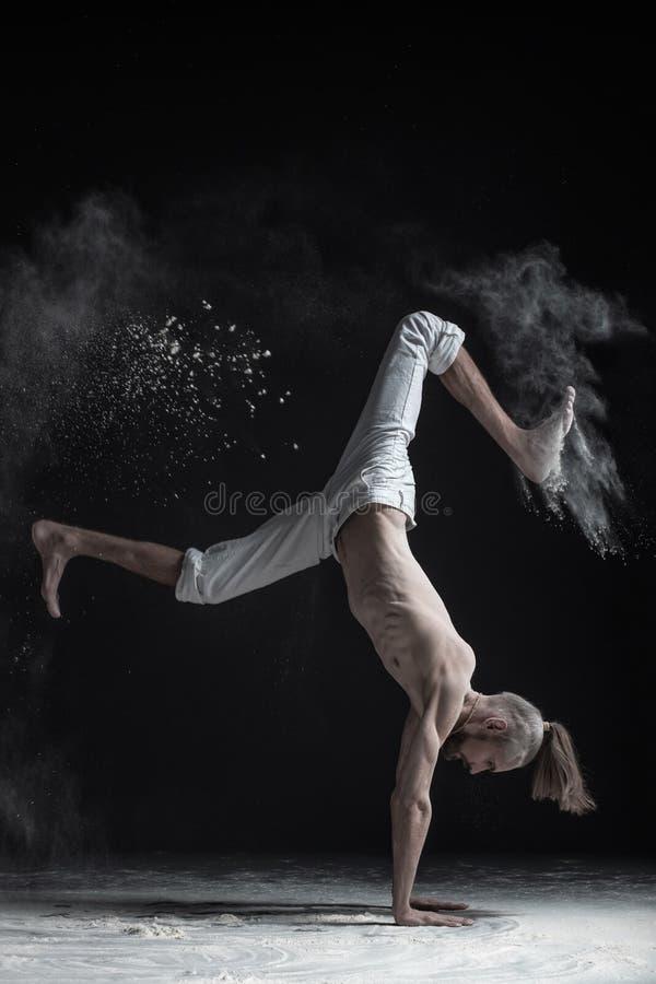 做手平衡asana vrischikasana的灵活的瑜伽人 免版税图库摄影