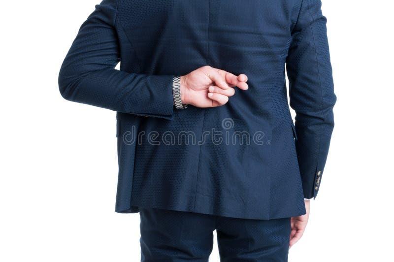 做手指的推销员或商人横渡了好运姿态 库存图片