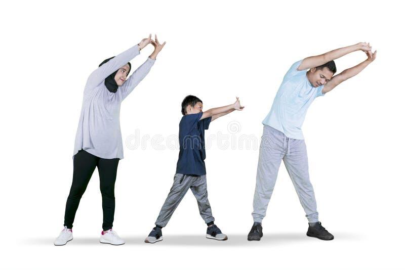 做手的小男孩舒展与他的父母 免版税库存图片