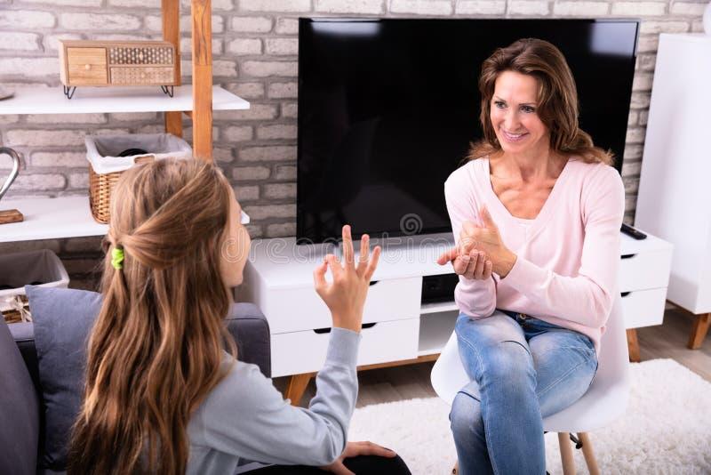 做手语的妇女和女孩 免版税库存图片
