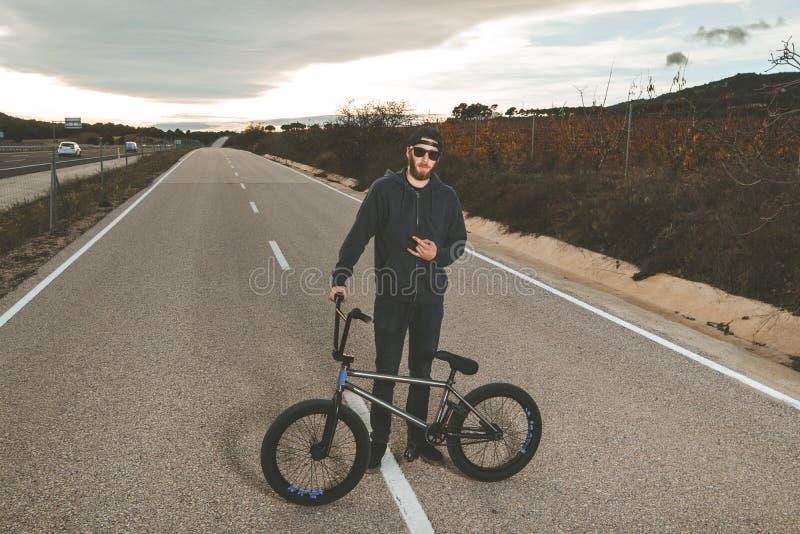 做把戏的BMX车手 有bmx自行车的年轻人 极其体育运动 库存照片