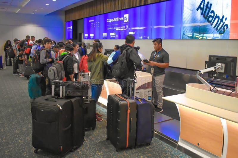 做报到的人们在巴拿马航空柜台在奥兰多国际机场 免版税库存图片