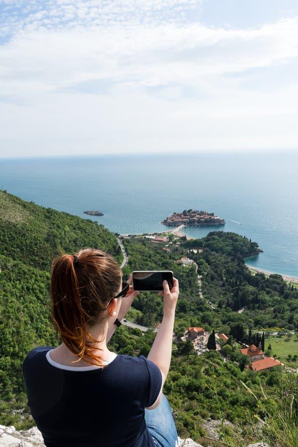 做拍的年轻白女孩与圣斯特凡岛智能手机的一张照片在布德瓦,黑山 绿色峭壁和令人惊讶的风景  免版税库存图片
