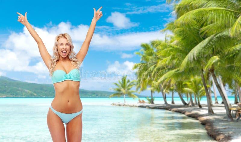 做拳头泵浦的比基尼泳装的愉快的年轻女人 免版税库存照片