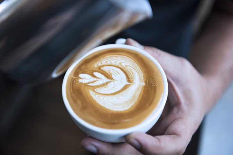 做拿铁或热奶咖啡艺术与泡沫的泡沫,咖啡杯的Barista在咖啡馆 免版税库存图片