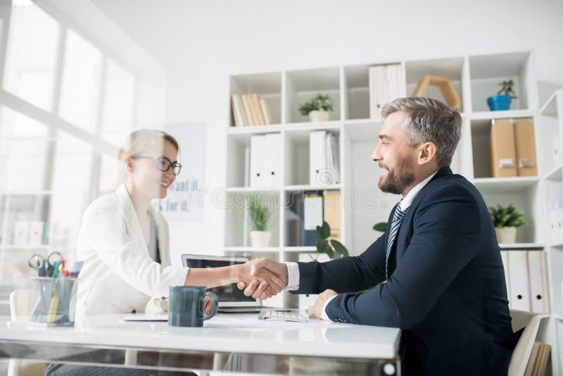 做握手的愉快的商务伙伴作为cooperatio的标志 库存图片