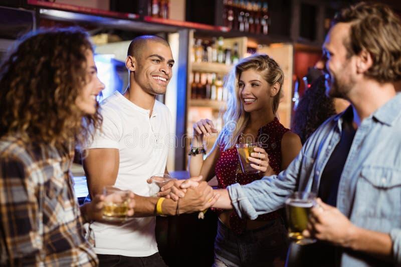 做握手的男性朋友在柜台的柜台在俱乐部 库存照片