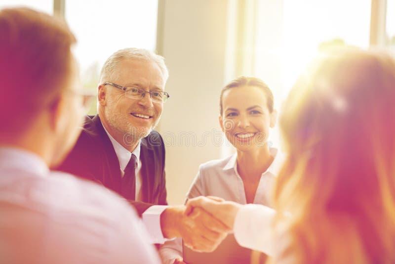 做握手的资深商人在办公室 免版税图库摄影
