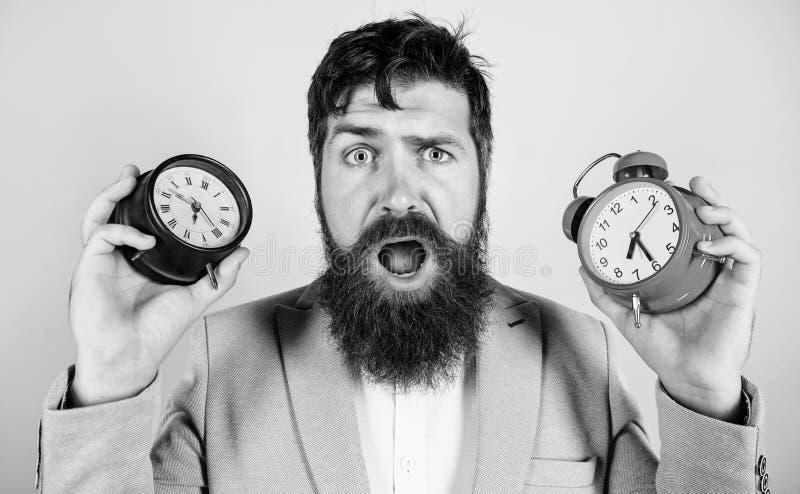 做改变的时钟混乱以您的健康 人有胡子行家举行两不同时钟 人不剃须的困惑的面孔 库存图片