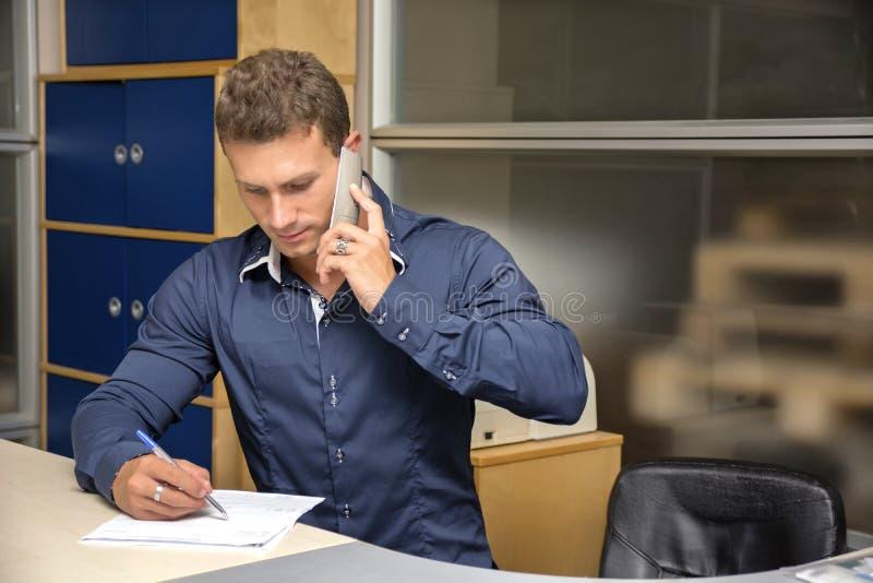 做文书工作的年轻人在办公桌,写 免版税库存图片