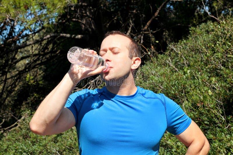 做断裂在训练期间,从瓶的饮用的新鲜的净水的运动员,休息并且享用新鲜空气 免版税库存照片