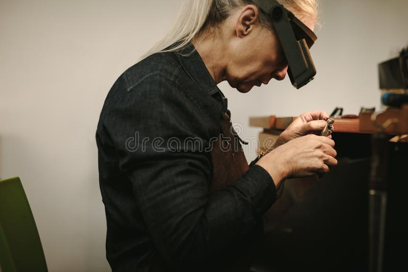 做新产品的资深女性珠宝商 库存图片