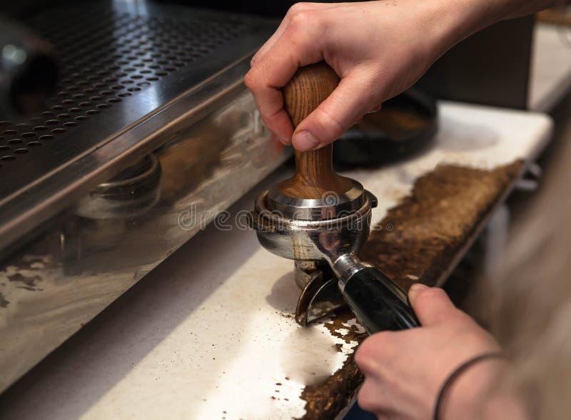 做新鲜的外带的咖啡的Barista 在手上的特写镜头视图有portafilter的, barista咖啡准备服务概念 免版税库存照片