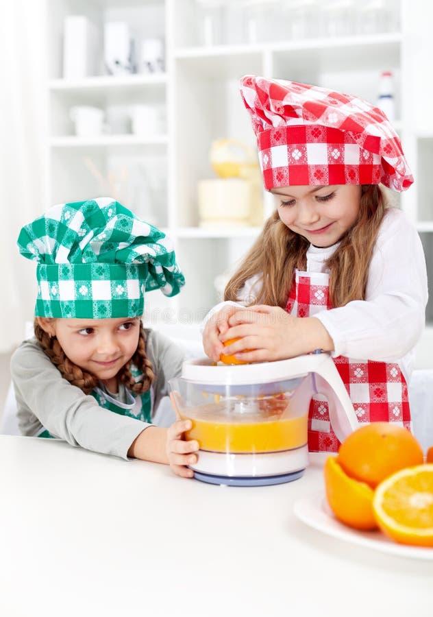 做新鲜的橙汁的小女孩 免版税库存照片