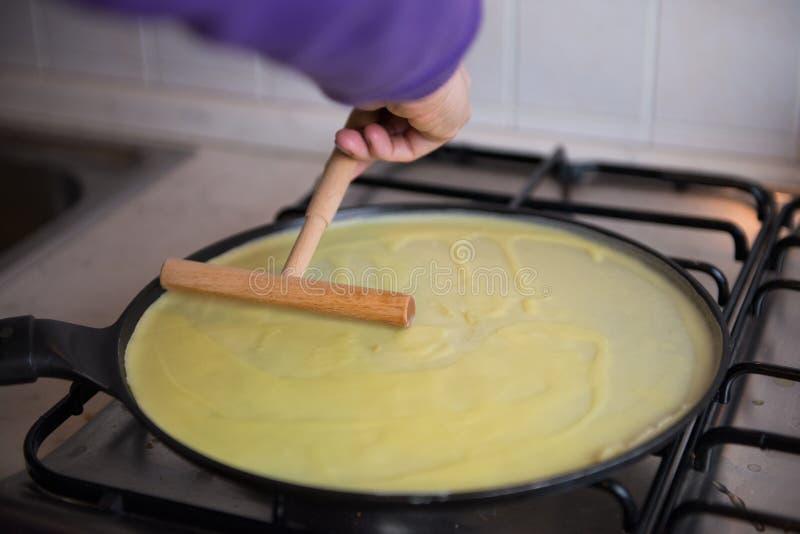做新鲜的自创稀薄的绉纱薄煎饼用木棍子 库存图片