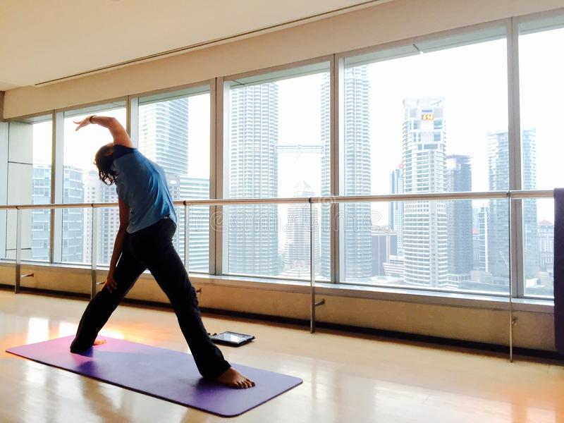 做旁边三角姿势的妇女在瑜伽演播室 免版税库存照片